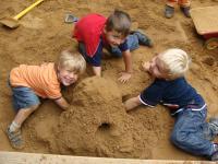 9 spielen im Sand